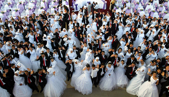 Brides and bridegrooms wave on the stage as they wait for their wedding ceremony in Ankara