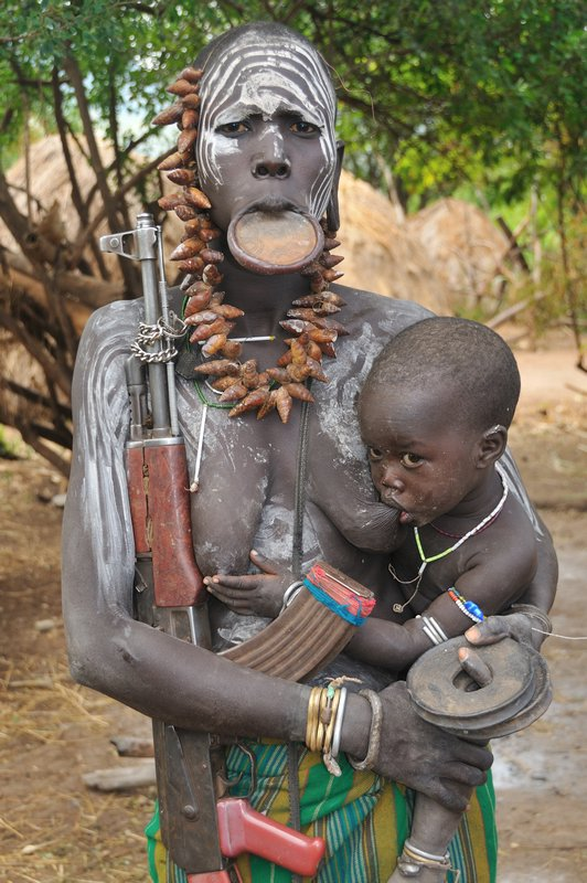 5740024-Mursi_woman_with_lip_plate-_suckling_babe_and_automatic_weapon_-_Mago_National_Park-_Om