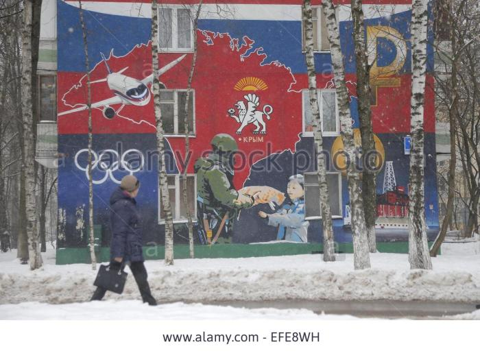 epa04594592-a-woman-walks-past-a-patriotic-graffiti-on-a-wall-of-an-EFE8WH.jpg